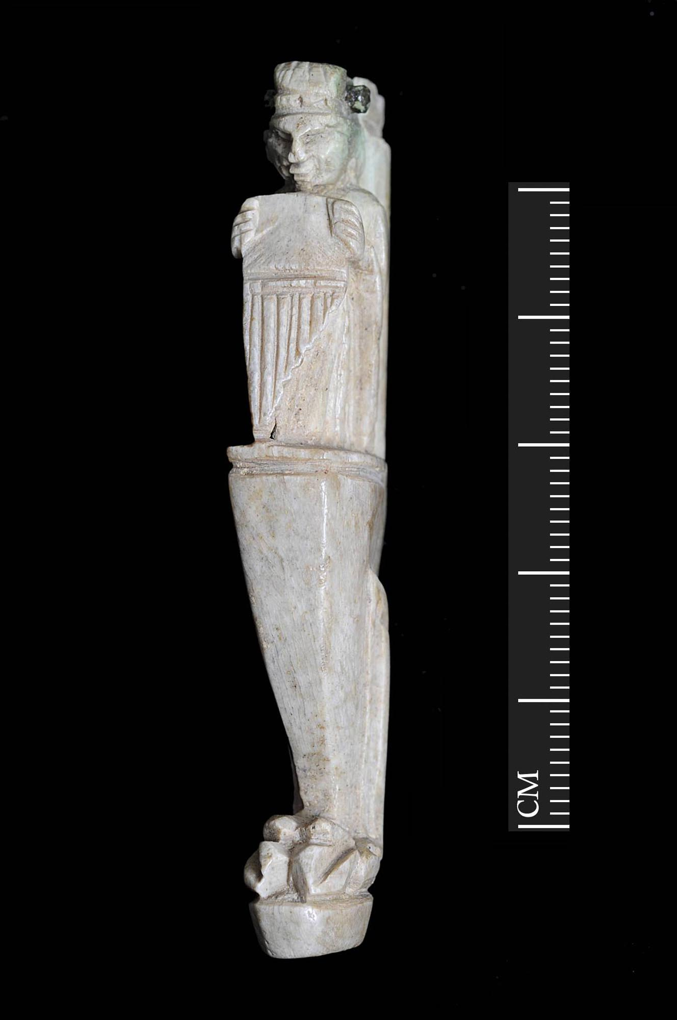 A carved bone handle for a folding knife. It depicts a grotesque figure holding a set of pan-pipes which is probably the Roman god Pan or another part-animal follower of the god Dionysus. Found during excavations for the Shires Shopping Centre - University of Leicester Archaeological Services