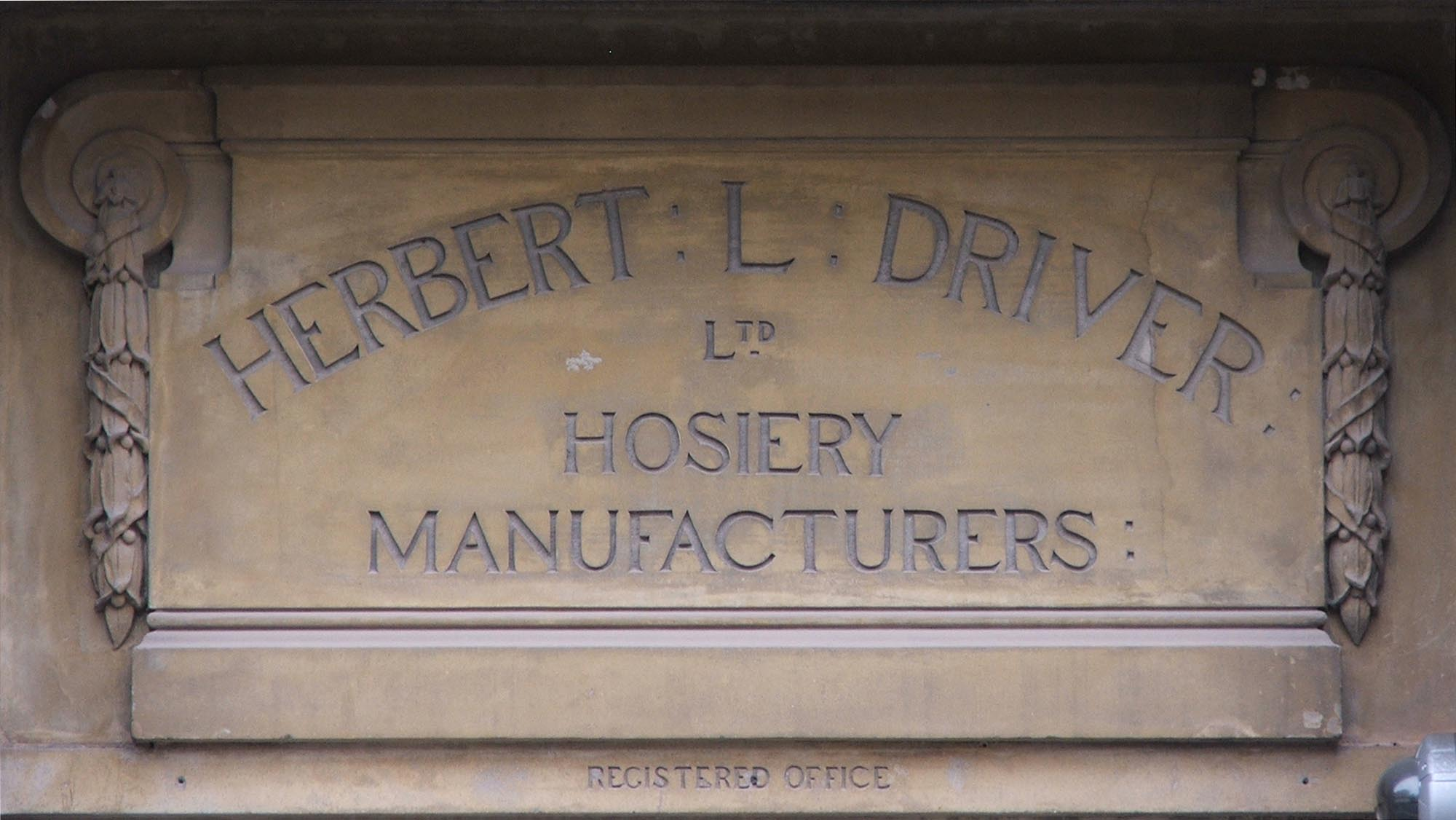 A carved sign for Herbert L.Driver Hosiery Manufactures Ltd. on King Street - Colin Hyde