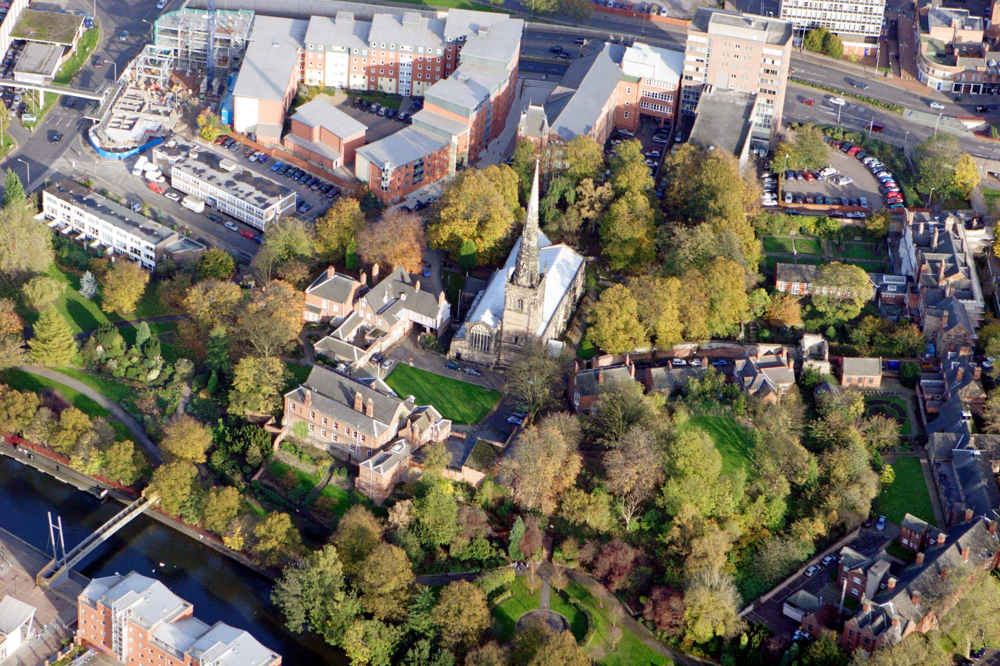 An aerial view of Leicester Castle from the west. The church of Mary de Castro is in the centre, with the Great Hall and Castle Gateway to the left and the castle motte surrounded by trees - University of Leicester Archaeological Services