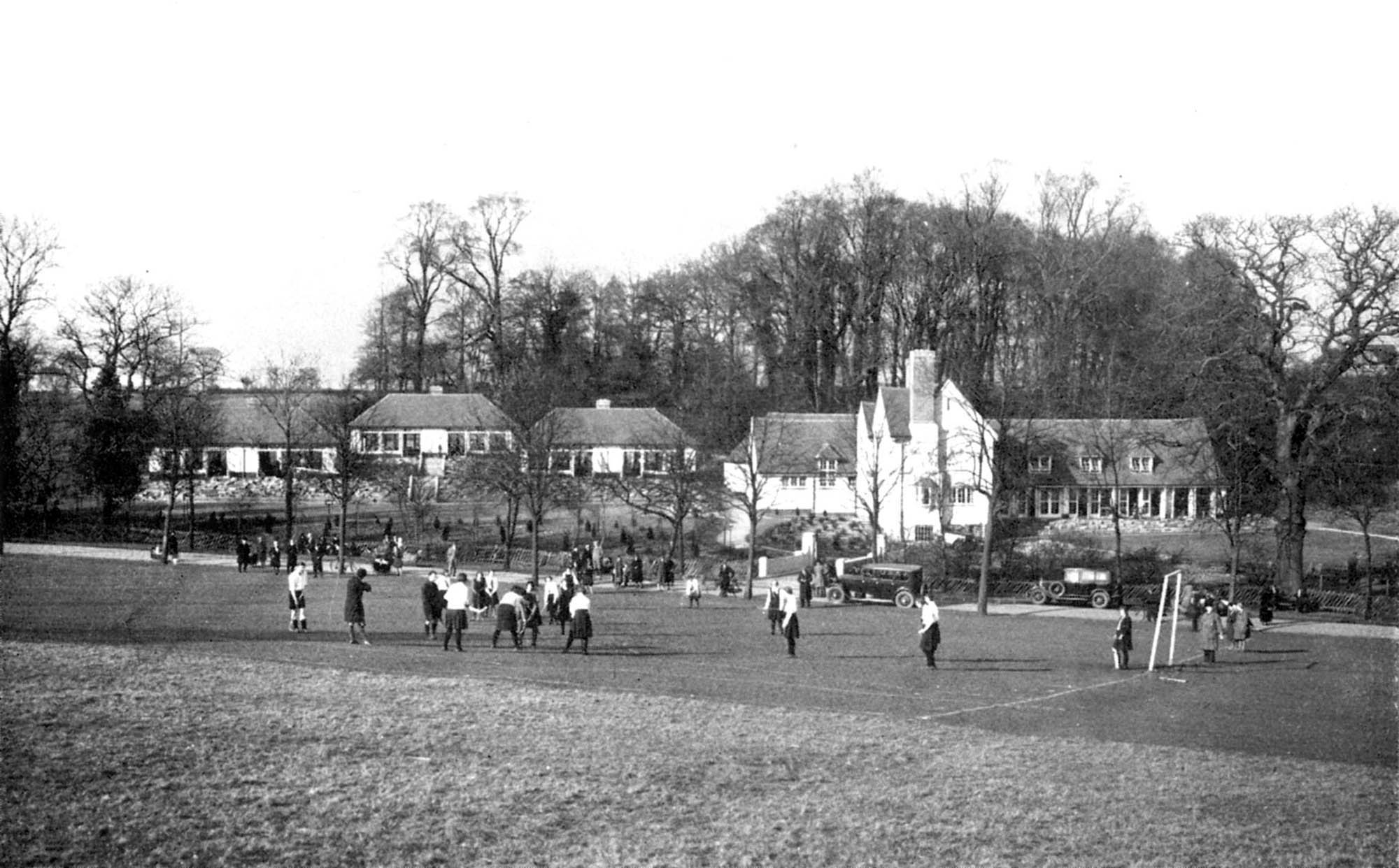 Pupils playing sports with the school buildings in the background, circa 1930s -